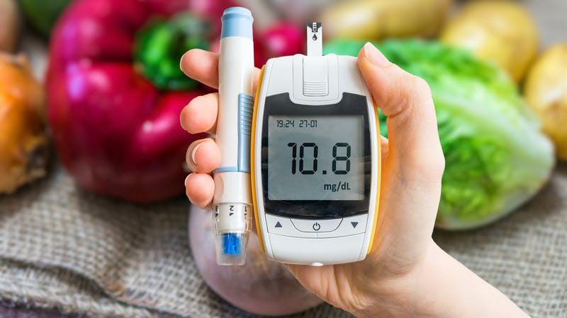 Diabetic diet, diabetes concept. Hand holds glucometer. Vegetables in background.