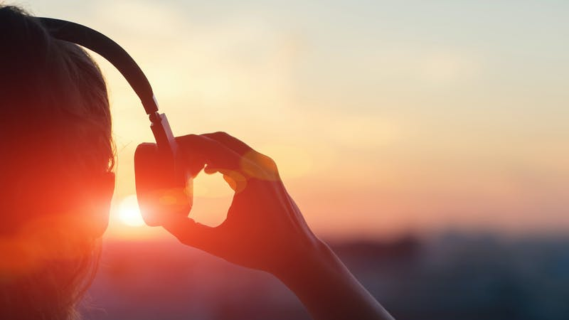 Girl with headphones in the sunrise
