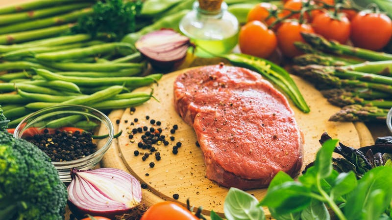 Raw rib eye steak with vegetables