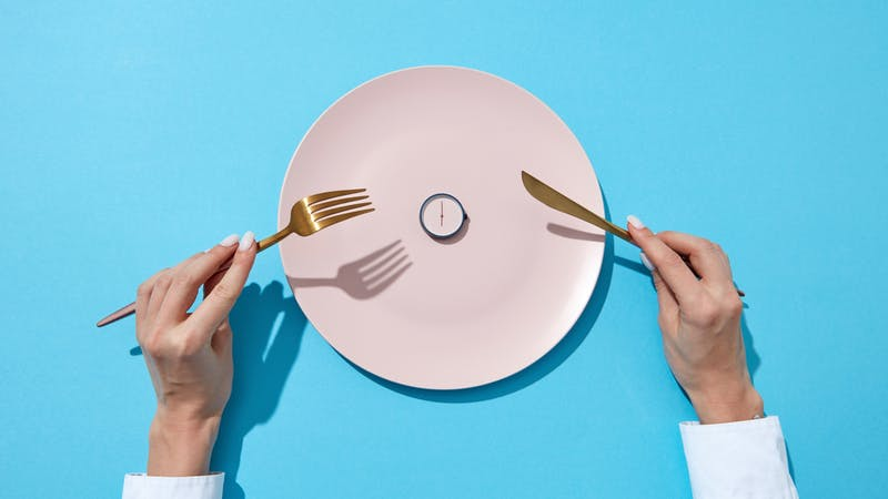 White plate with round whatch shows six o'clock served knife and fork in a girl's hands on a blue background. Time to eat and diet concept. Top view.