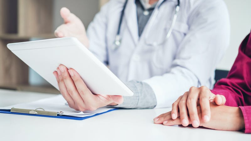 Doctor consulting with patient presenting results on digital tablet tablet  sitting at table
