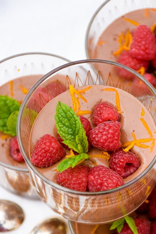 Low-carb chocolate pudding with raspberries and orange zest