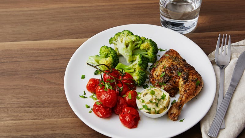 Roasted chicken legs and cherry tomatoes with garlic-butter