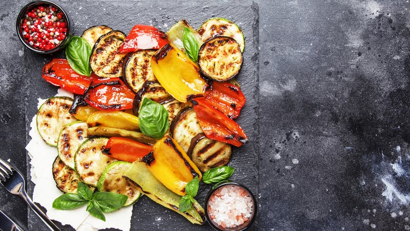 Grilled multicolored vegetables, aubergines, zucchini, pepper with green basil on serving stone board