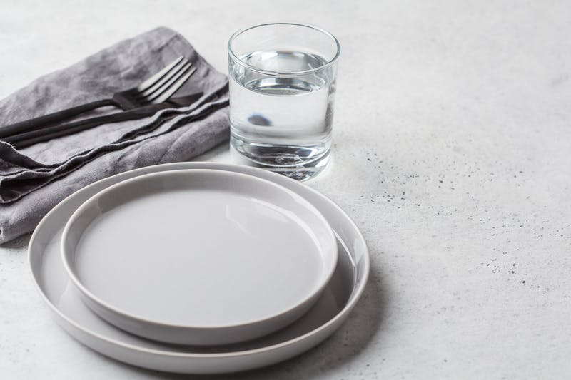 Empty plate and glass of water, white background. Medical fasting concept.