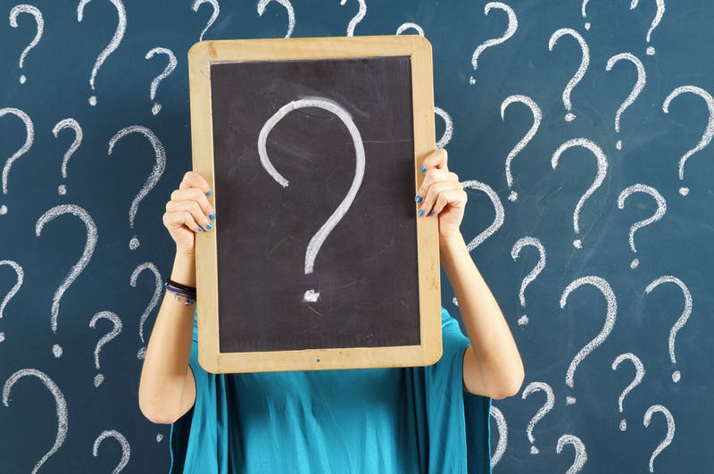 Woman holding chalkboard with question mark