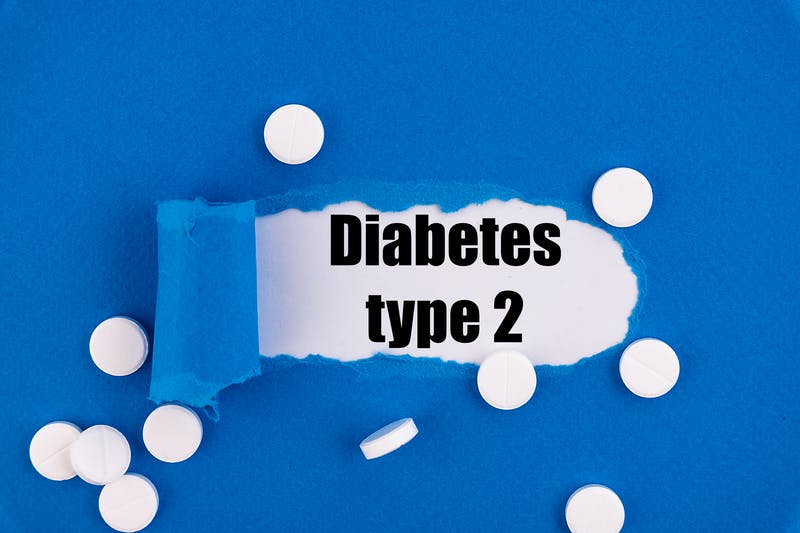The text Diabetes type 2 appearing behind torn blue paper.