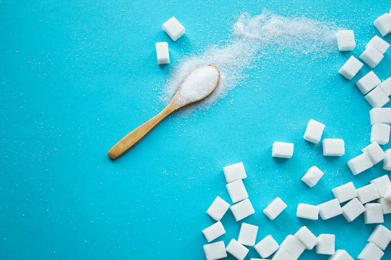 White sugar with spoon on blue background.