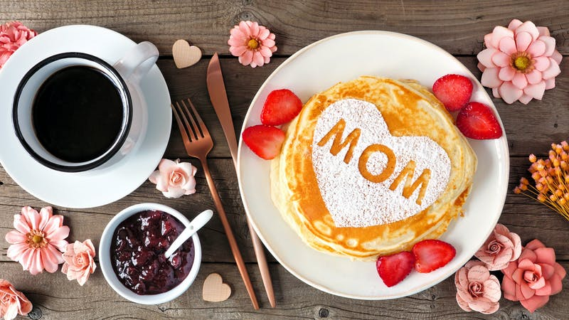 Mothers Day breakfast pancakes with heart shape and MOM letters, overhead view table scene on rustic wood