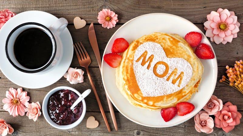 有心形和MOM字母的母亲节早餐煎饼,俯瞰质朴的木头上的桌子