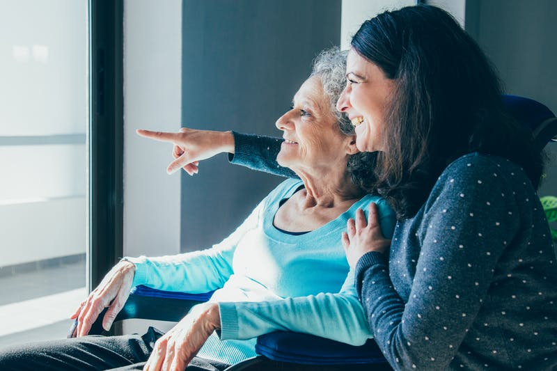Joyful woman taking care of elderly mother
