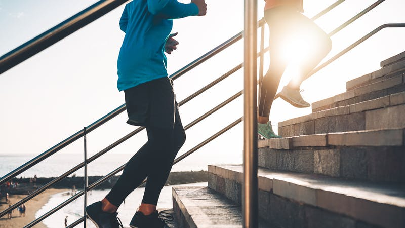 View of runners legs training outdoor – Young couple doing a workout session on stairs next the beach at sunset – Healthy people, jogging and sport lifestyle concept