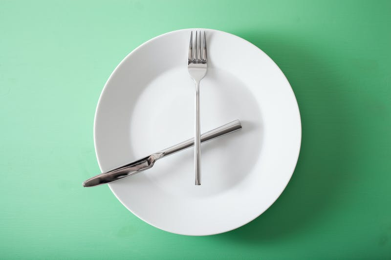 concept of intermittent fasting and ketogenic diet, weight loss. fork and knife crossed on a plate