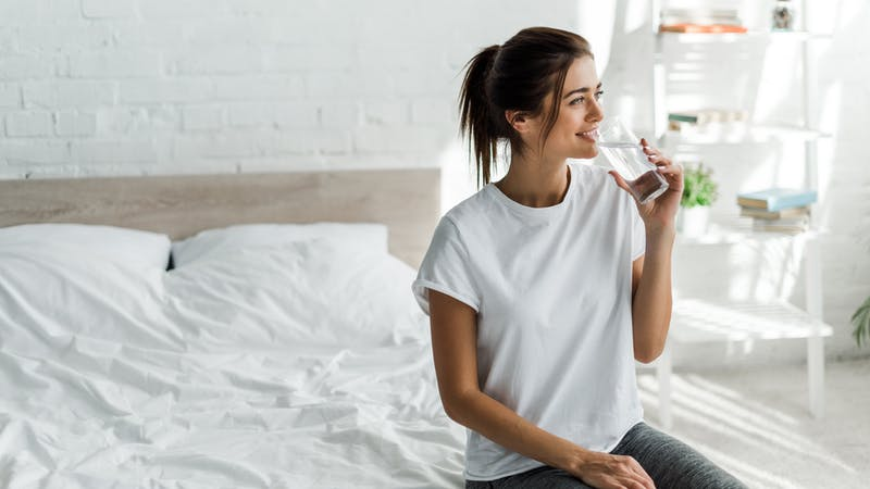 beautiful happy girl holding drinking water from glass in the morning