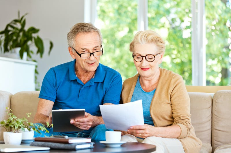 Retired couple watching bills and calculating monthly expenses