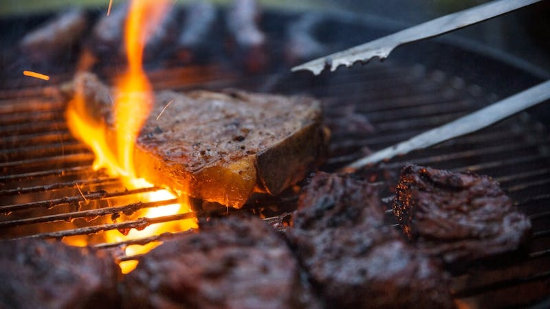 Flame Grilled Steaks Being Flipped On Barbecue With Tongs