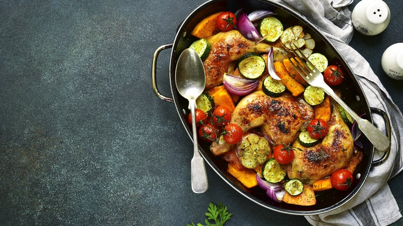 Chicken legs roasted with vegetables in a skillet pan