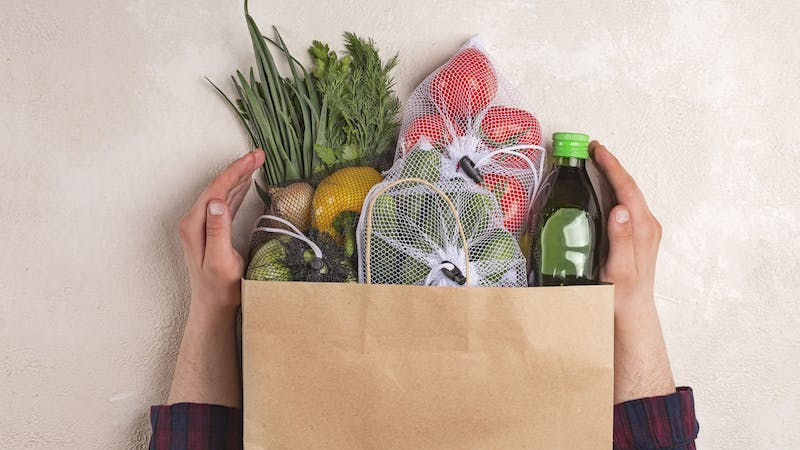 Man holds products in a paper bag. Vegetables in the range of shopping in the terrestrial and online store. top view