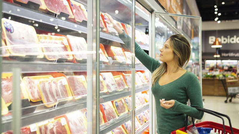 Young woman in a supermarket buying meat
