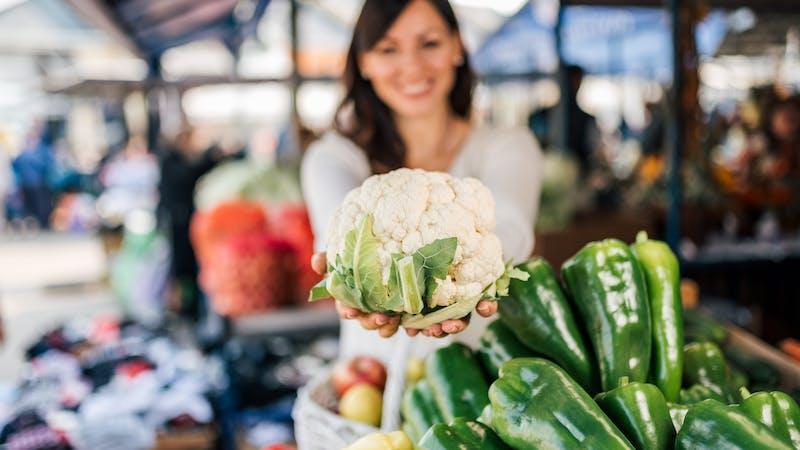 Buying cauliflower at farmers market. Focus on the cauliflower.