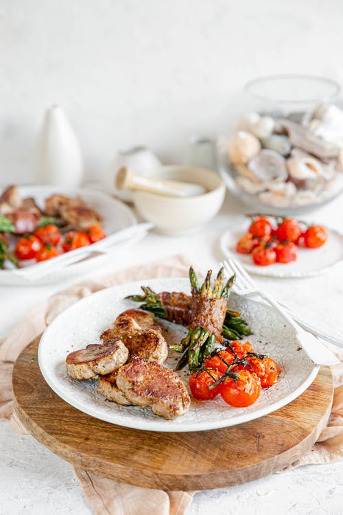 Pan-seared pork loin with bacon-wrapped green beans and baked tomatoes