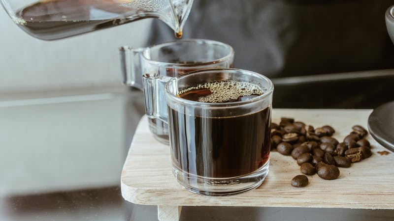 Cropped shot of Barista pouring a hot coffee after drip in a glass cup of coffee.