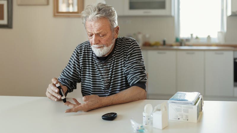 Senior man with glucometer