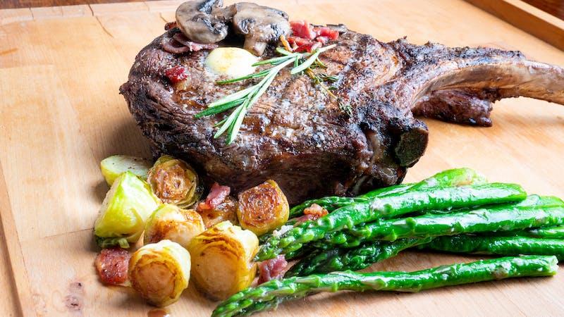 Huge Cowboy Cut Rib Eye Beef Steak with Ketogenic Vegetables on a Plate