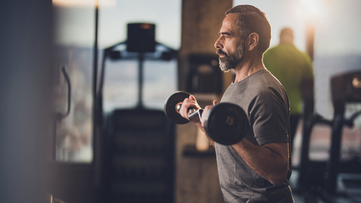 Active senior man having strength exercise with barbell in a gym.