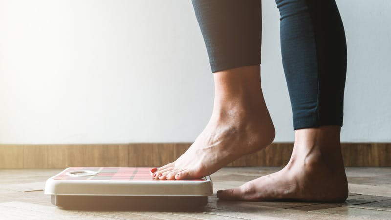 Female checking kilogrammes getting on the scale – self care and body positivity concept – warm flare on left
