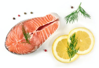 Salmon steak with lemons, dill, and peppercorns, on white