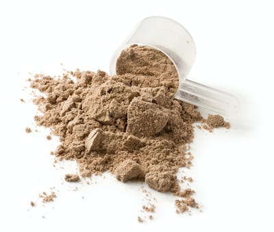 Measuring scoop of protein powder on a white background