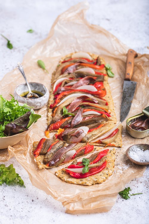 Mediterranean high protein pizza with roasted vegetables and anchovies