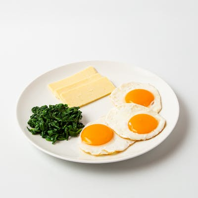 female vegetarian breakfast with cheese eggs and spinach